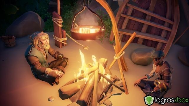 Cocina comida en una hoguera durante la noche.